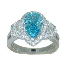 Pear shaped irradiated blue diamond accented with a trapezoid cut diamond and round brilliant cut diamonds.